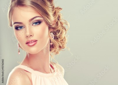 Fototapeta Beautiful model with elegant hairstyle . Beautiful woman with fashion wedding hairstyle and colourful makeup