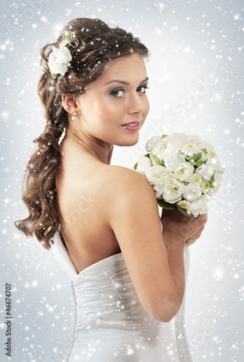Fototapeta A young woman in a bridal dress on a snowy background
