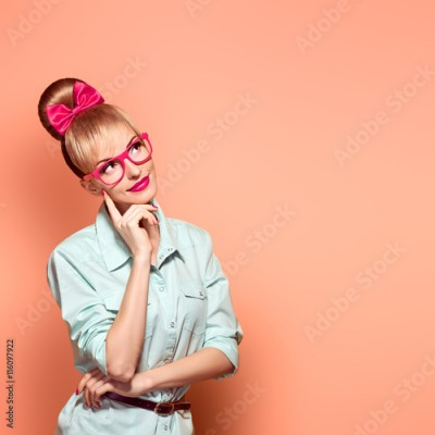 Fototapeta Fashion. Nerd woman in Stylish Glasses Having Fun. Hipster fashion girl think, idea. Playful Blonde nerd with Glamour Pinup stylish Hairstyle, Trendy fashion Outfit, Red bow Makeup. Unusual Creative