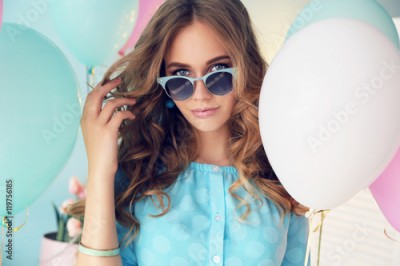 Fototapeta fashion interior photo of beautiful young girl with dark curly hair and tender makeup, posing with colorful air balloons
