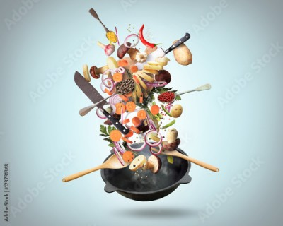 Fototapeta Large iron skillet with falling vegetables and mushrooms
